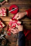 装饰圣诞节礼物和12月的小男孩和妇女的手 免版税库存照片