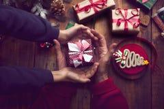 装饰圣诞节礼物和12月的小男孩和妇女的手 库存照片