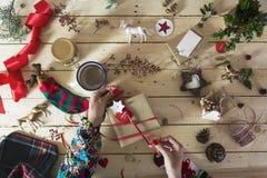装饰圣诞节礼物的妇女,围拢由欢乐deco 库存图片