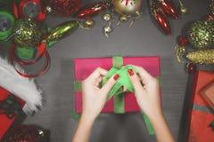 装饰圣诞节礼物的少妇一个箱子 库存图片