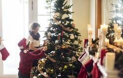 装饰圣诞节装饰品树的人们 免版税库存照片