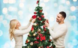 装饰在光的愉快的夫妇圣诞树 图库摄影