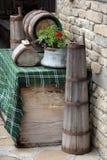 装饰在庭院里 用于过去的传统保加利亚装置-老奶油搅乳棒、木酒桶和caludron 图库摄影