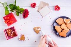 装饰在心脏形状的顶视图女性手自创曲奇饼作为恋人的礼物在华伦泰` s天 白色木桌与 免版税库存图片