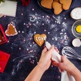 装饰在心脏形状的顶视图女性手自创曲奇饼作为恋人的礼物在华伦泰` s天 黑暗的石背景w 库存照片