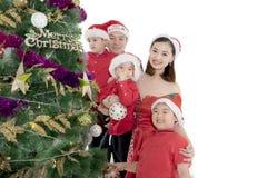 装饰在演播室的亚洲家庭一棵圣诞树 免版税库存图片