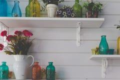 装饰在白色墙壁上的架子的葡萄酒减速火箭的玻璃瓶 图库摄影