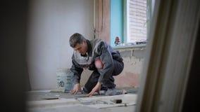 装饰地板的被集中的建造者在屋子里建设中有瓦片的 股票录像