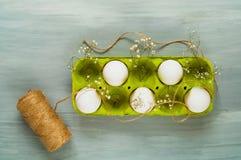 装饰复活节假日,在一个绿色箱子的鸡蛋在轻的木背景,顶视图,文本的空白 免版税图库摄影