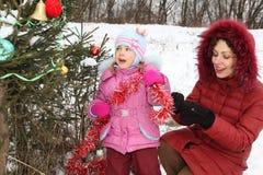 装饰女孩的christmass她的母亲结构树 免版税库存照片