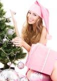 装饰女孩辅助工圣诞老人结构树的圣诞节 免版税图库摄影