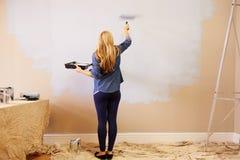 装饰室的妇女使用在墙壁上的漆滚筒 免版税库存照片