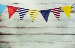 装饰宴会的五颜六色的旗子线有白色木f 库存照片