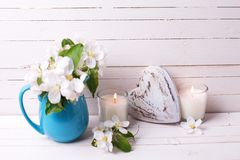 装饰心脏、苹果树花和蜡烛在白色木 免版税图库摄影