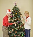 装饰愉快的高级结构树的圣诞节夫妇 免版税图库摄影