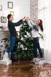 装饰愉快的结构树的圣诞节夫妇 微笑的男人和妇女 免版税库存照片