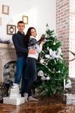 装饰愉快的结构树的圣诞节夫妇 微笑的男人和妇女 免版税图库摄影