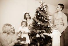 装饰新年树的家庭 库存图片