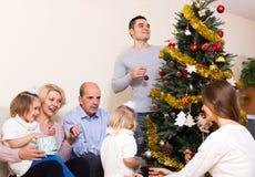 装饰新年树的家庭 免版税库存照片