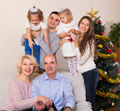 装饰新年树的家庭 免版税库存图片