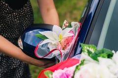 装饰有人造花和布的一辆婚姻的汽车的过程 库存照片