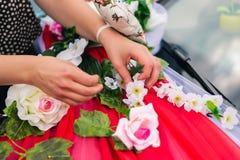 装饰有人造花和布的一辆婚姻的汽车的过程 免版税图库摄影