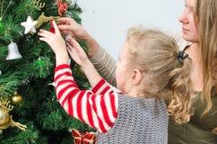 装饰树的小女孩和她的母亲 免版税库存照片