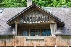 装饰母牛响铃在一个高山山小屋的屋顶下 库存照片