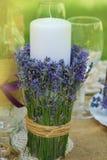 装饰淡紫色玻璃,用淡紫色开花与蜡烛在一个桌和绿色Blured夏天Bakground 免版税图库摄影