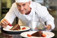装饰点心的微笑的男性点心师在厨房里 免版税图库摄影