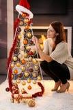 装饰现代圣诞树的俏丽的妇女 免版税库存图片