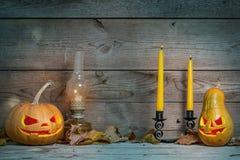 装饰的南瓜夫妇在神秘的秋天背景的万圣夜与蜡烛和煤气灯 免版税库存照片