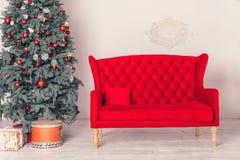装饰的圣诞树和一个红色沙发 库存照片