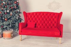 装饰的圣诞树和一个红色沙发 免版税图库摄影