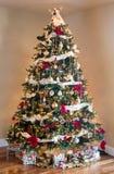 装饰的圣诞树在现代客厅 免版税库存照片