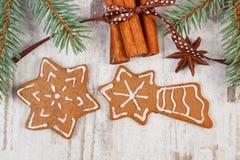 装饰的姜饼,云杉的分支,在老木背景,圣诞节装饰的香料 免版税库存照片