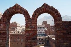 装饰的房子和宫殿瞥见在曲拱墙壁后在老城Sana'a,也门 库存照片