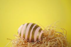装饰的手画脸红与金条纹的桃红色复活节彩蛋在秸杆巢反对与拷贝空间的明亮的黄色背景 库存照片