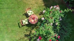 装饰的桌用乳酪、草莓和酒在美丽的玫瑰园,浪漫日期桌食物设置空中顶视图里  免版税库存图片