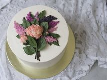 装饰的白色奶油蛋糕与buttercream花-丁香,牡丹-在与鞋带织品的木背景 葡萄酒 库存图片