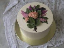 装饰的白色奶油蛋糕与buttercream花-丁香,牡丹-在与鞋带织品的木背景 葡萄酒 库存照片