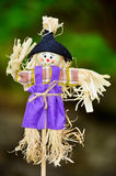 装饰的穿戴的稻草人在一个绿色春天庭院里 库存图片