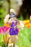 装饰的穿戴的稻草人在一个绿色春天庭院里 免版税库存照片