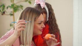 装饰的蓝色油漆鸡鸡蛋的母亲关闭,由她的女儿决定的奔跑兔宝宝耳朵的,说某事和他们开始 影视素材