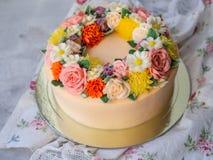 装饰的黄色奶油蛋糕与buttercream花-牡丹,玫瑰,菊花,康乃馨-在白色木背景 免版税库存图片