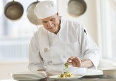装饰盘的厨师在商业厨房里 免版税图库摄影