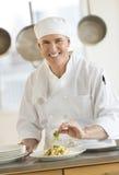 装饰盘的厨师在柜台在商业厨房里 免版税库存照片