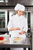 装饰盘的女性厨师在柜台 免版税库存照片