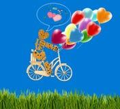 装饰矮小的人的图象一辆自行车和气球的反对天空 库存图片