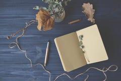 装饰笔记本和对象在木书桌上的 激动人心的葡萄酒工作场所 免版税库存照片